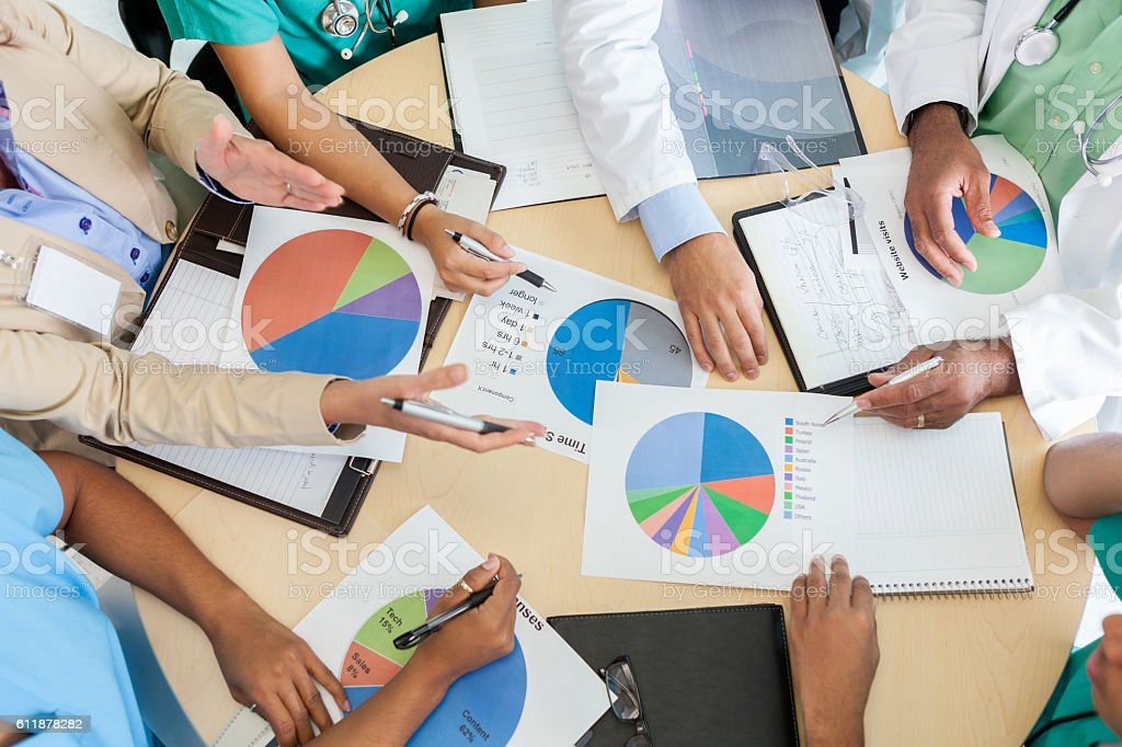 Medical staff and hospital administrators review charts during meeting stock photo