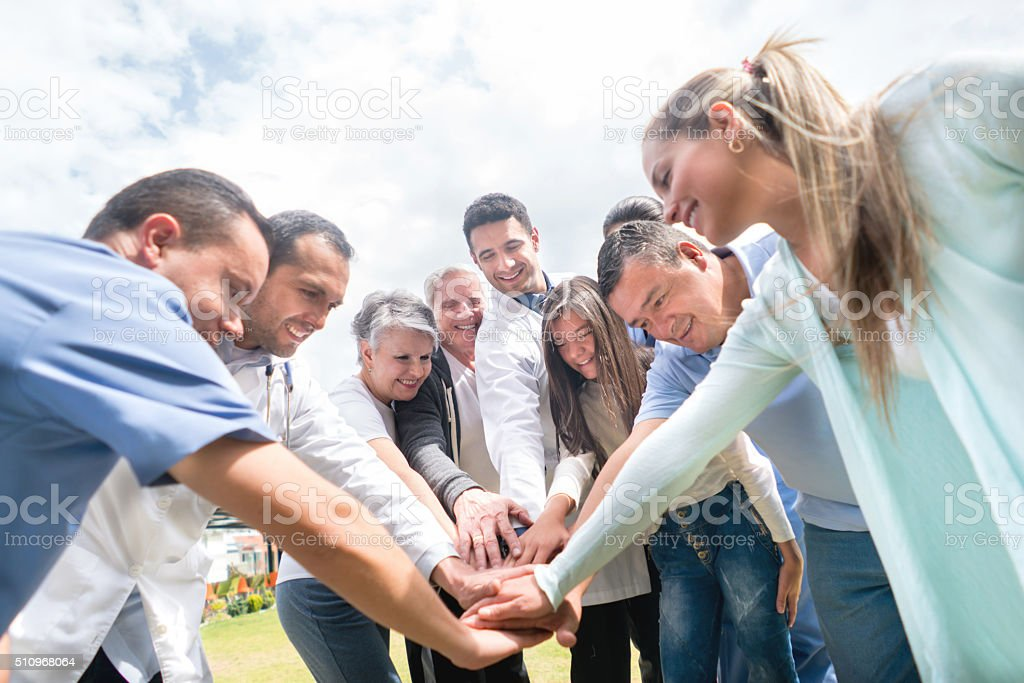 Medical staff and patients with hands together stock photo