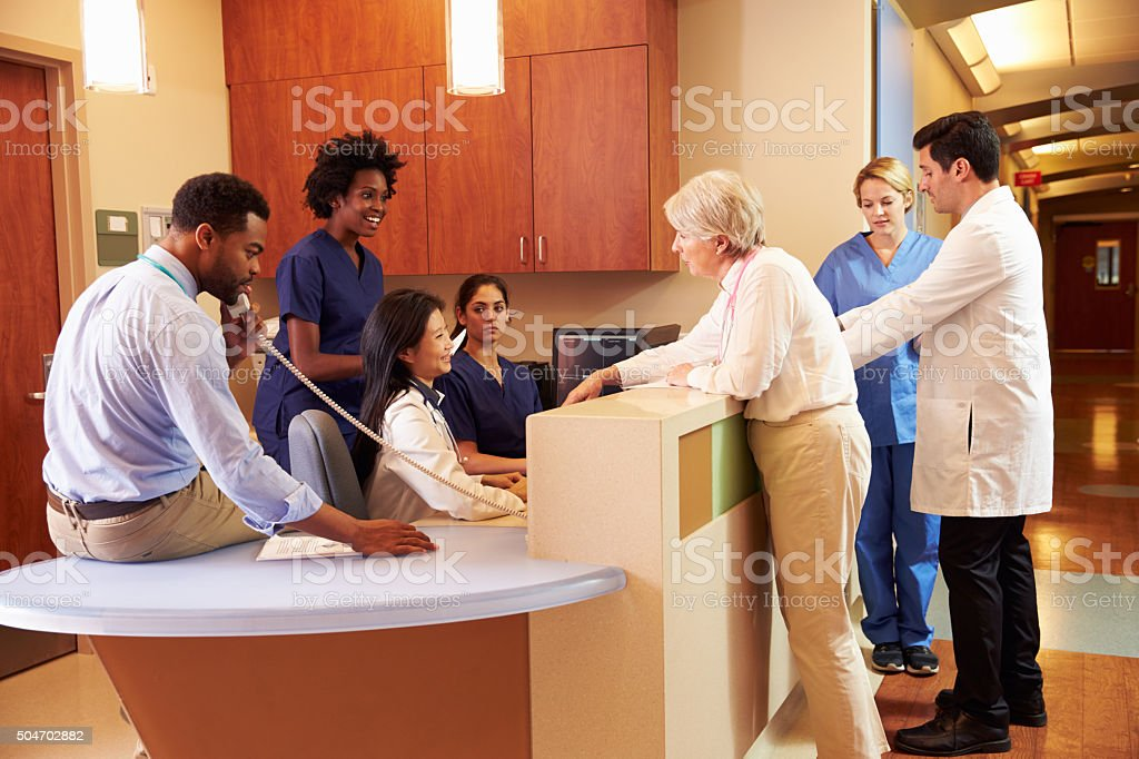 Medical Staff At Busy Nurse's Station In Hospital stock photo