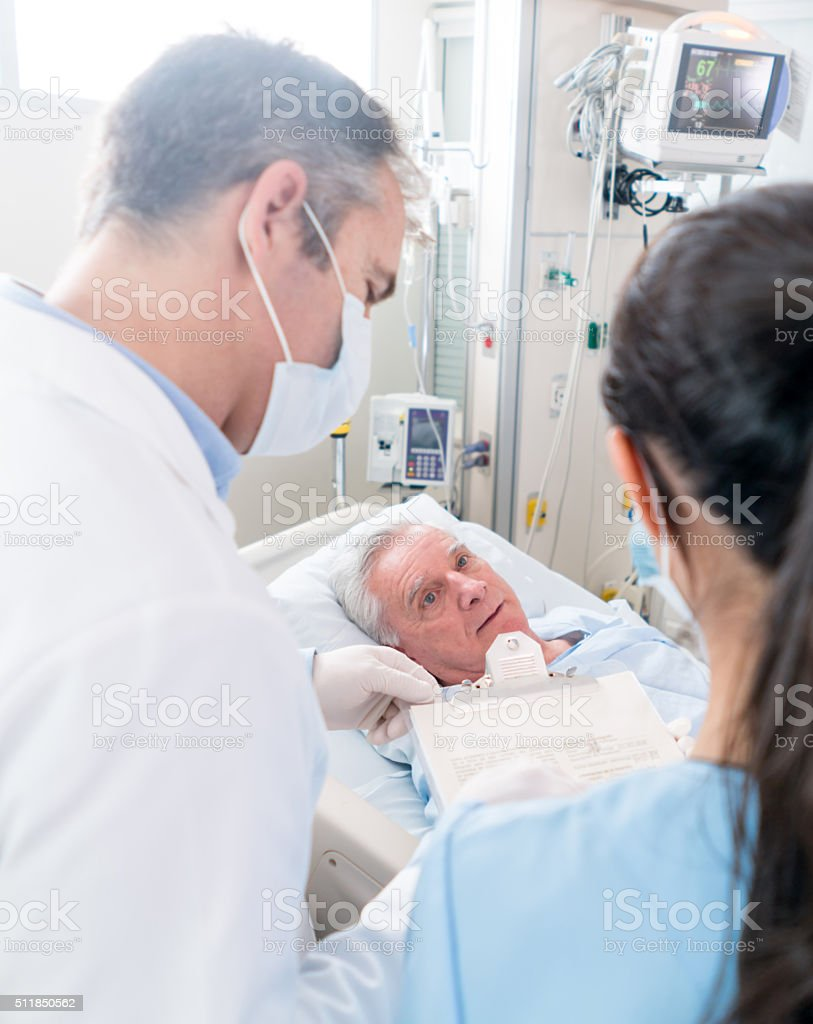 Medical staff checking on patient at the ICU stock photo