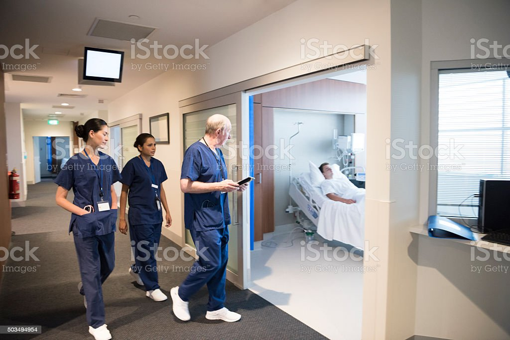 Medical staff in hospital corridor with patient in bed stock photo