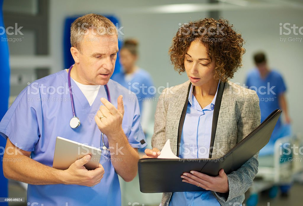 a mature hospital doctor is chatting with a suited woman who could be...