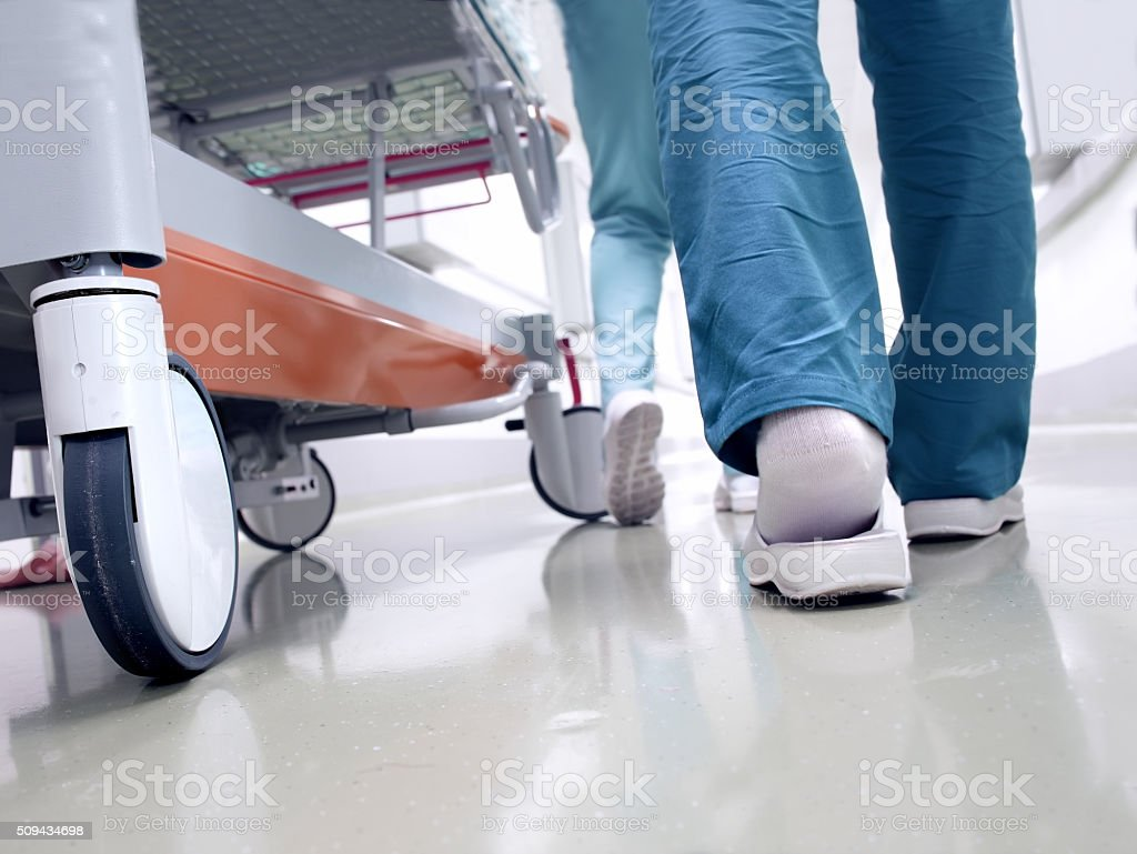 Medical staff moving patient through hospital corridor stock photo
