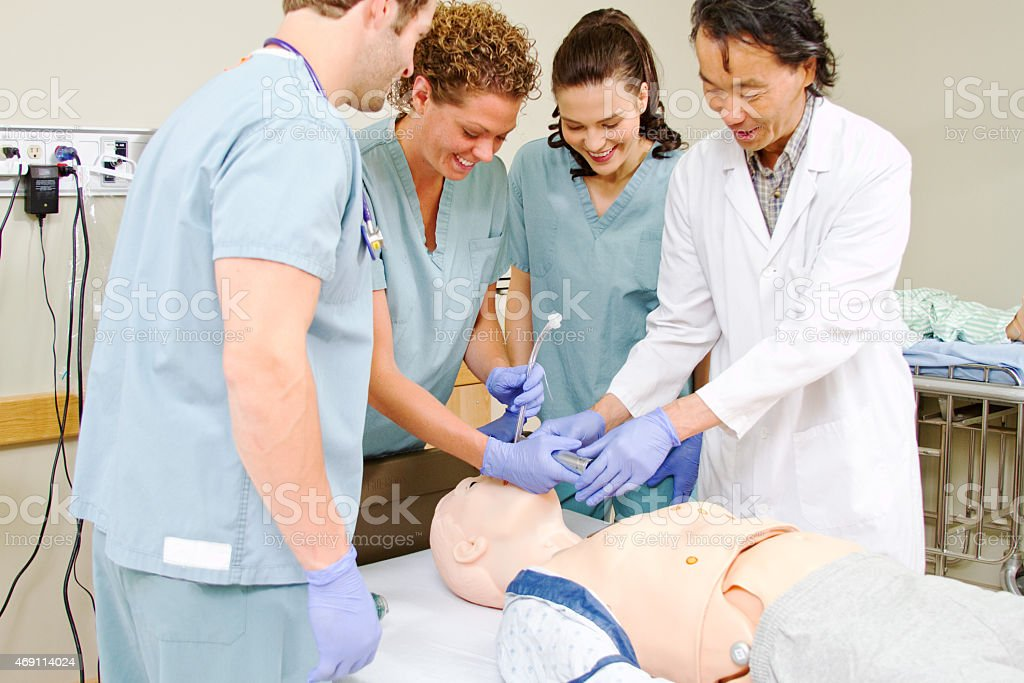 Medical staff practice intubating mannequin stock photo