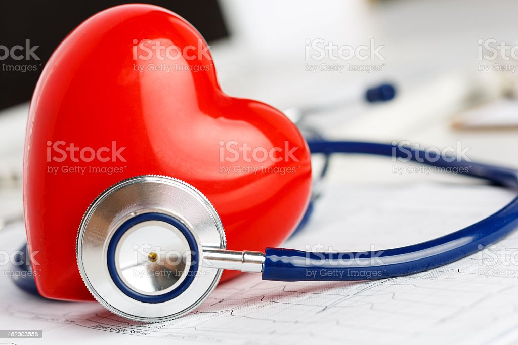 Medical stethoscope and red toy heart lying on cardiogram chart stock photo