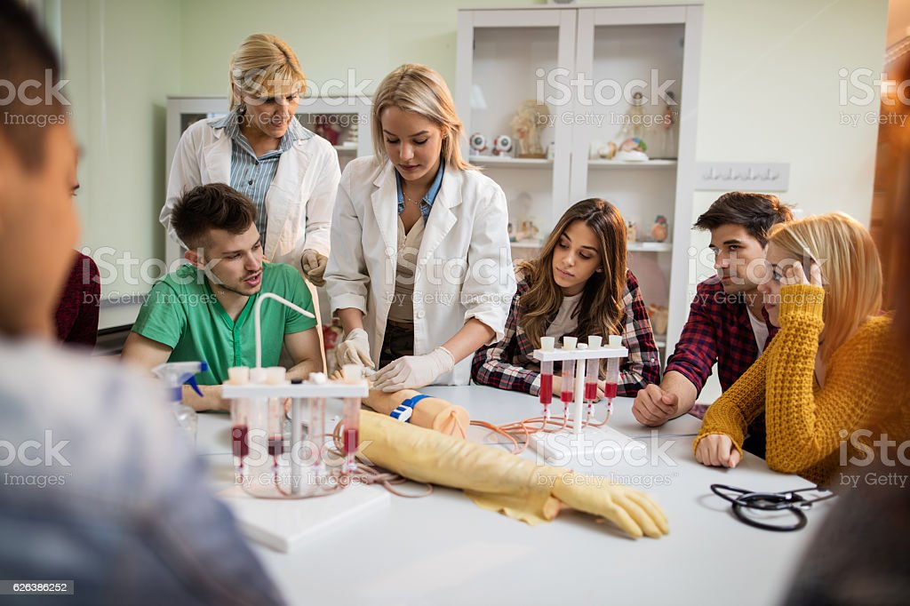 Medical student learning to take blood from artificial hand. stock photo