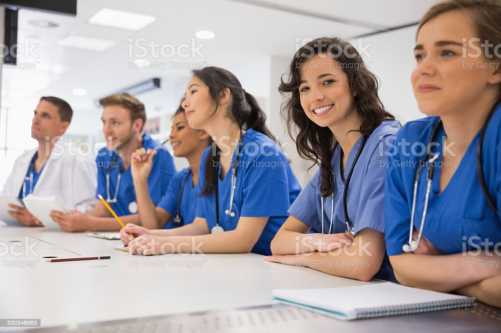 Medical student smiling at the camera during class stock photo