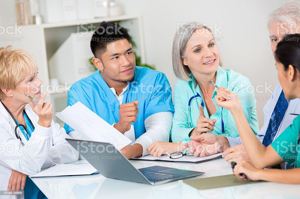 Diverse team of nurses, doctors and administrators discuss...