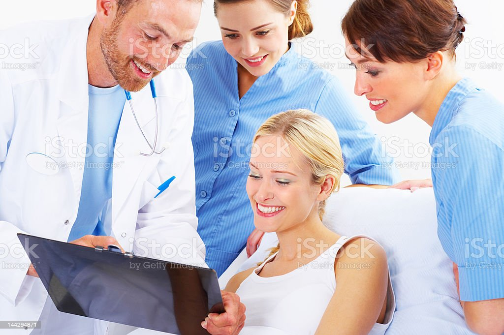 Medical team discussing a patient's charts with her royalty-free stock photo