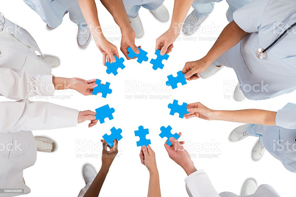 Medical Team Holding Blue Jigsaw Pieces In Huddle stock photo