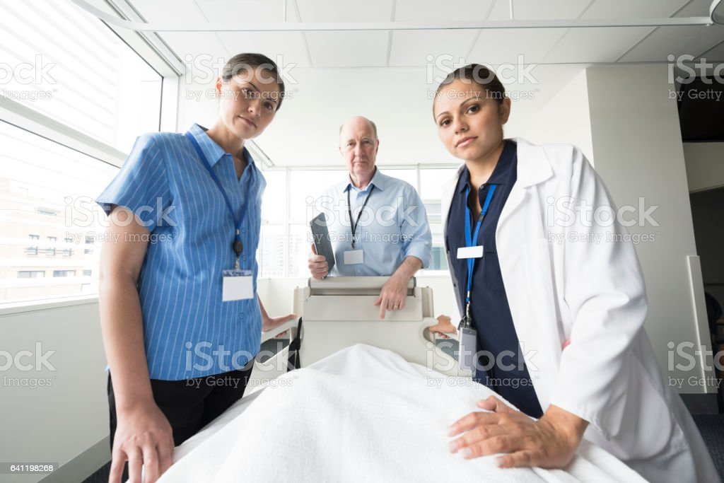 Medical team listening to patient in bed, personal perspective stock photo