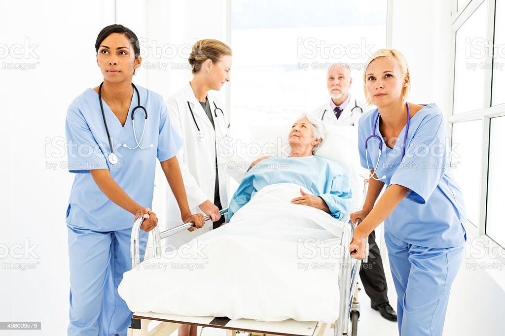 Medical Team Pushing Patient On Hospital Gurney stock photo