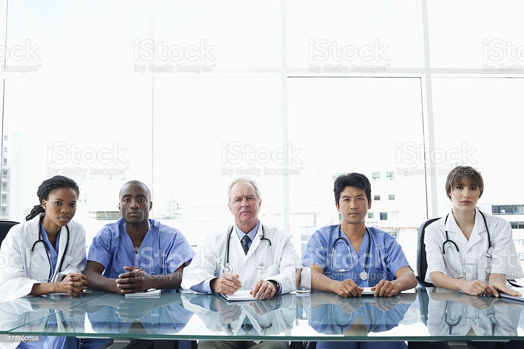 Medical team sitting seriously at a desk stock photo