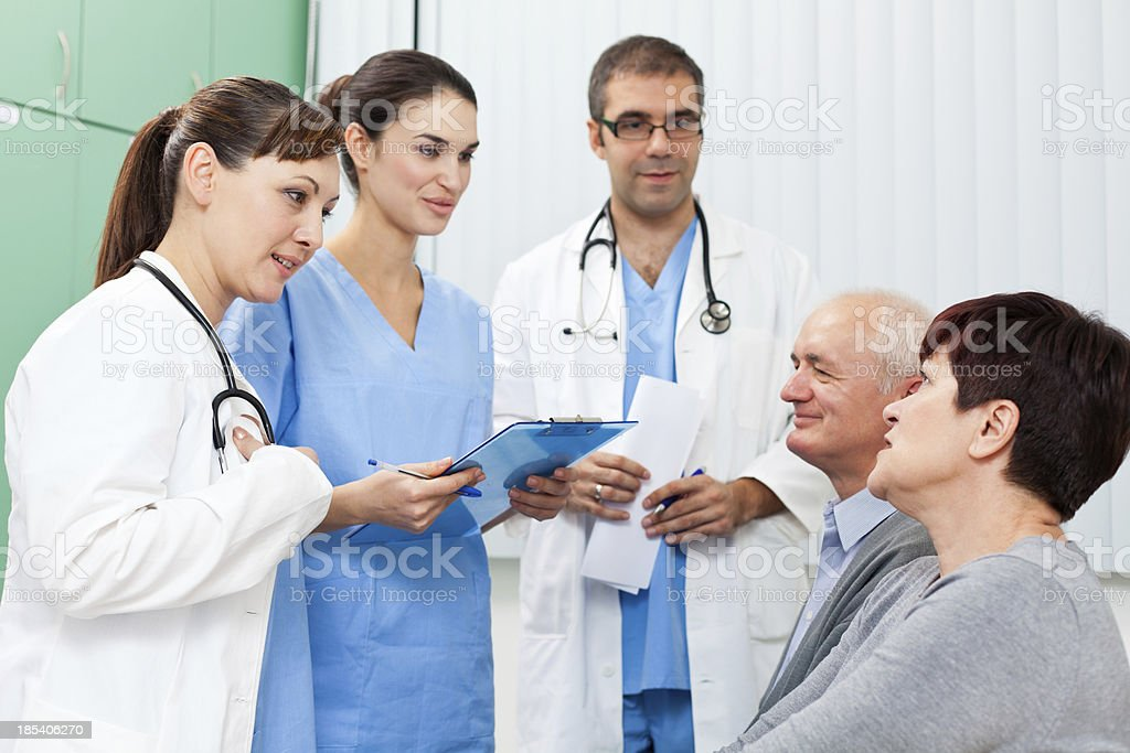 Medical team talking with patients in the waiting room royalty-free stock photo
