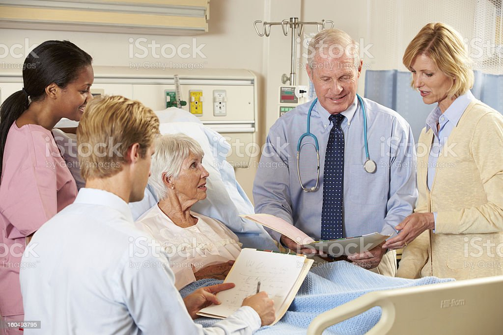 Medical Team Visiting Senior Female Patient In Bed stock photo