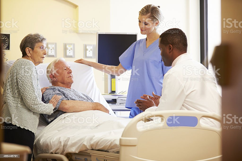 Medical team with elderly couple in hospital room stock photo