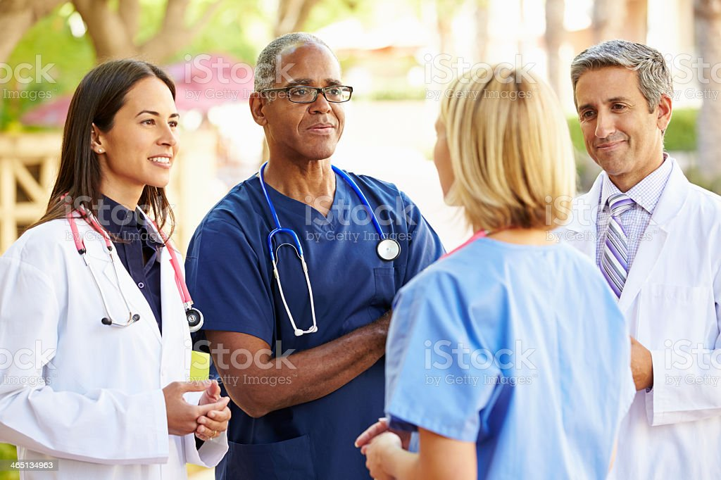 A medical team with stethoscope talking outdoors stock photo