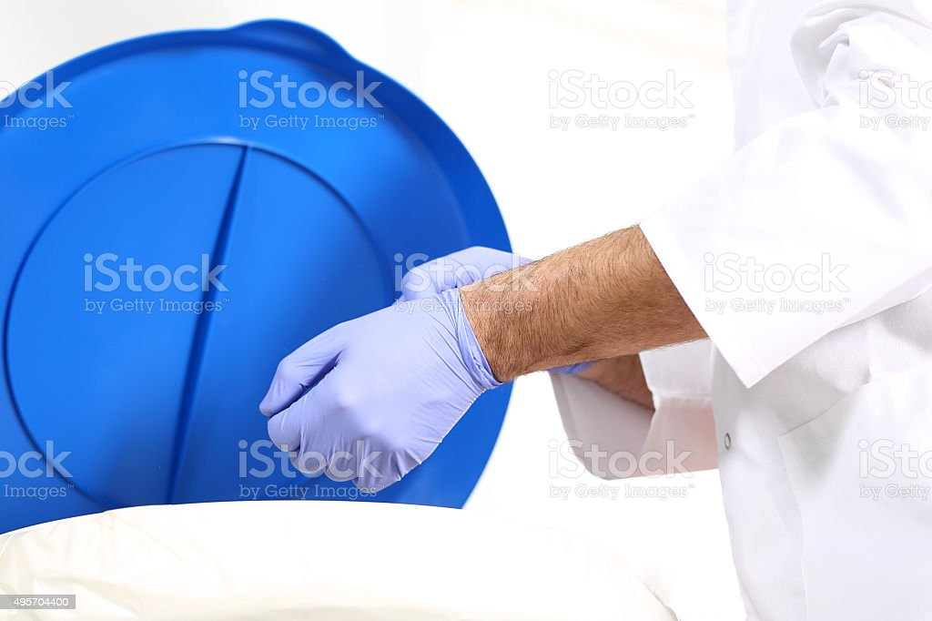 Medical waste, surgeon dropping the gloves in a special container stock photo