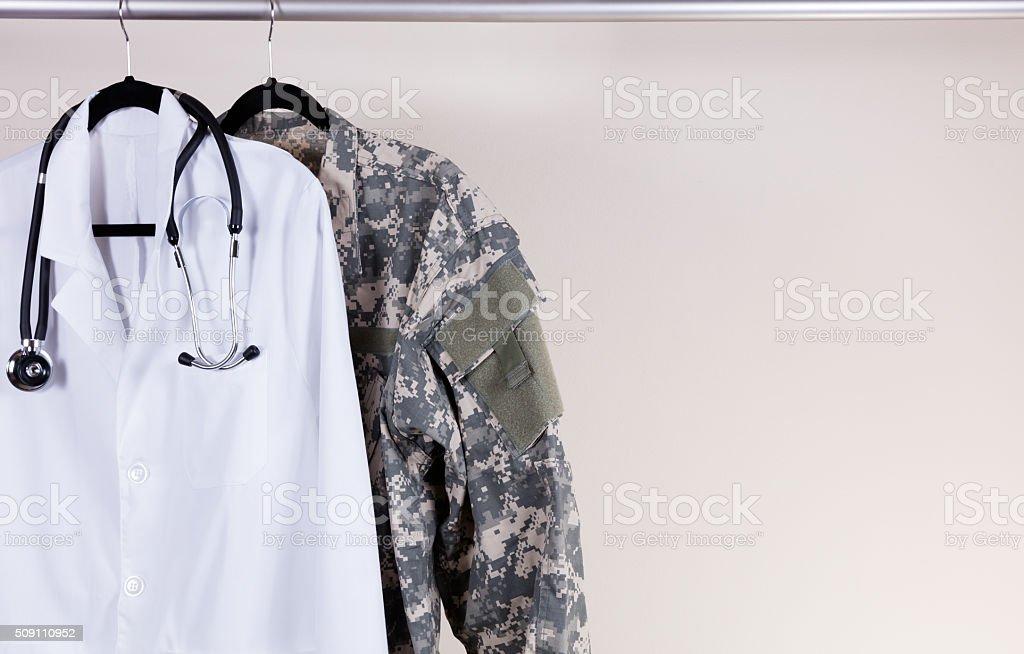 Medical white consultation coat and military uniform on hanger stock photo