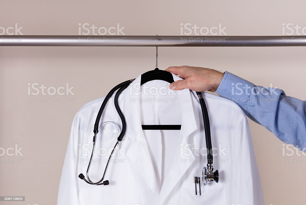 Medical white consultation coat with stethoscope being taken off stock photo