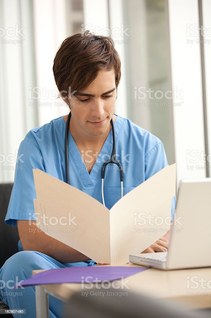 Medical worker in the hospital looking at a file stock photo