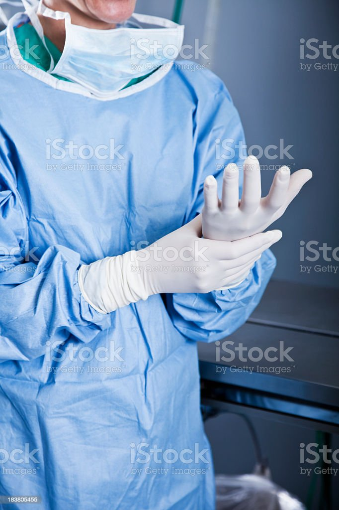 Medical worker putting on latex gloves stock photo