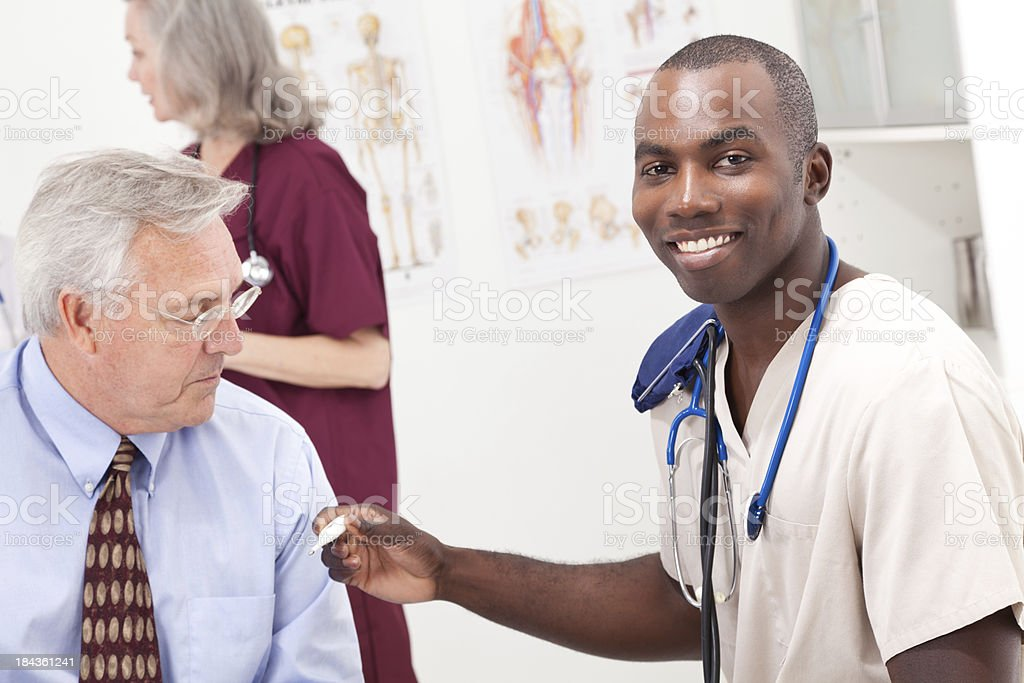 Medical Worker Taking Patient's Temperature stock photo