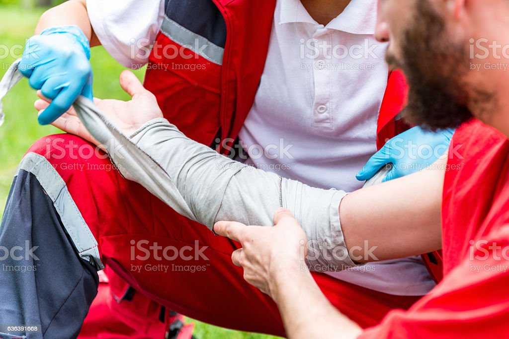 Medical worker treating burns on man's hand stock photo