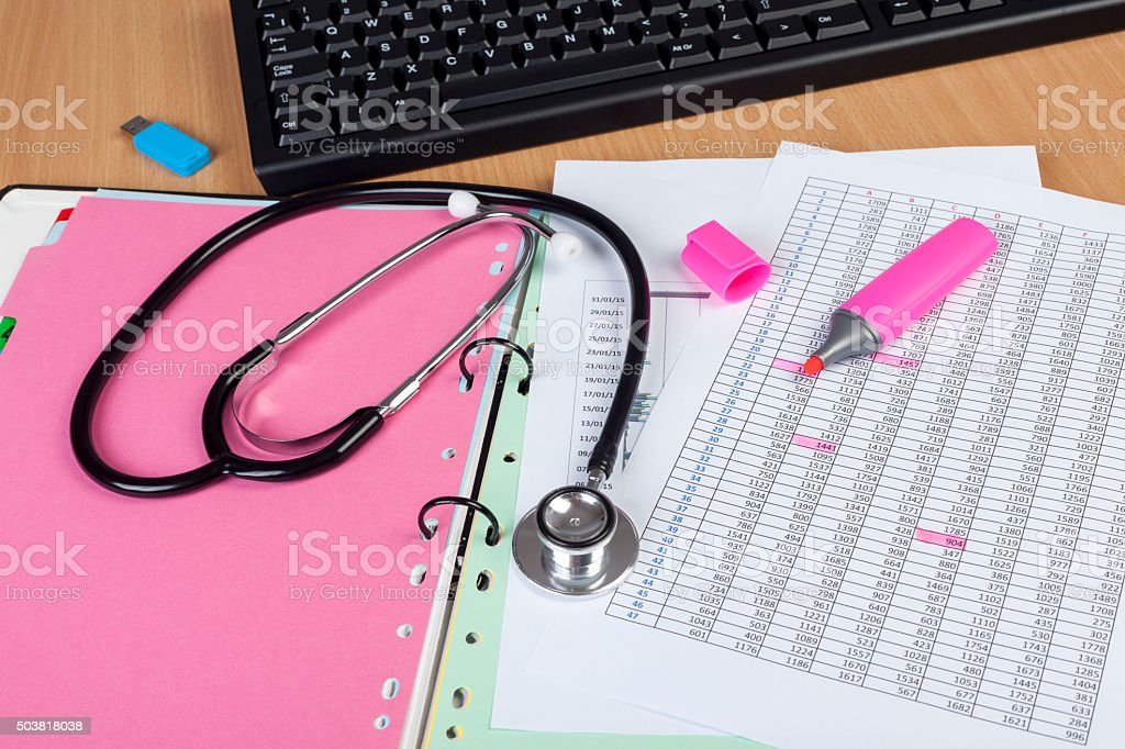 Medical workers desktop showing stethoscope and some financial r stock photo