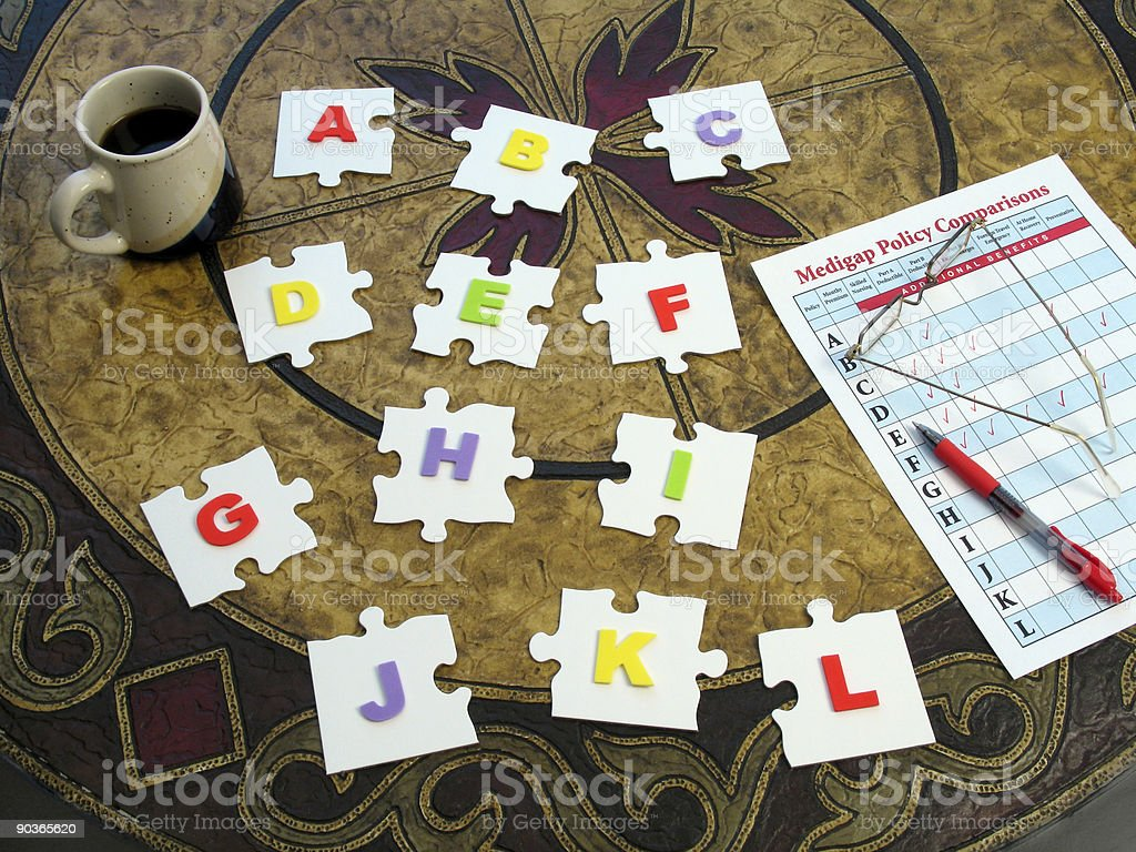 Medicare Medigap Puzzle: Puzzle Pieces with Alphabetical Plan Letters royalty-free stock photo