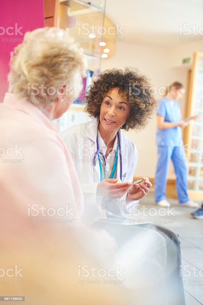 A female doctor sits in doctor's clinic advising her senior patient...