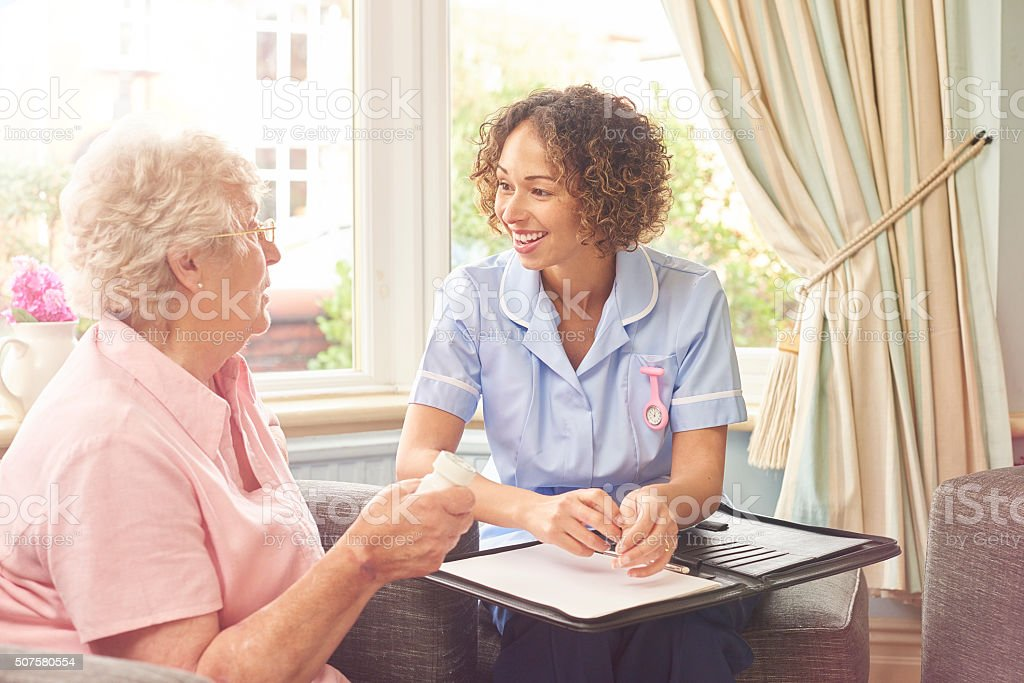 a senior woman in her home explains to a care nurse what medicine she...