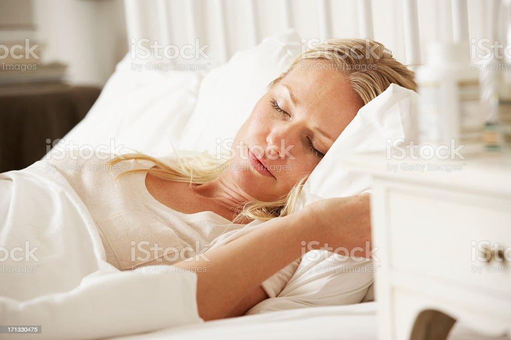 Medication On Bedside Table Of Sleeping Woman stock photo