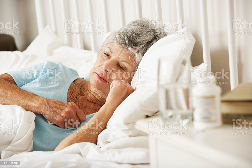 Medication On Bedside Table Of Sleepless Senior Woman royalty-free stock photo