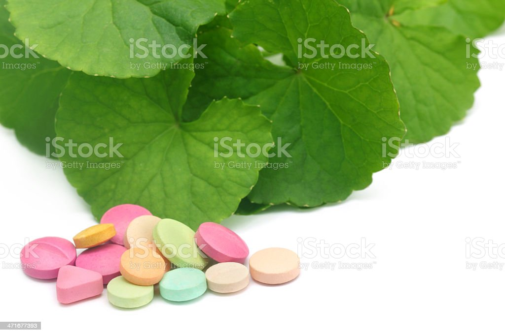 Medicinal thankuni leaves with colorful pills stock photo