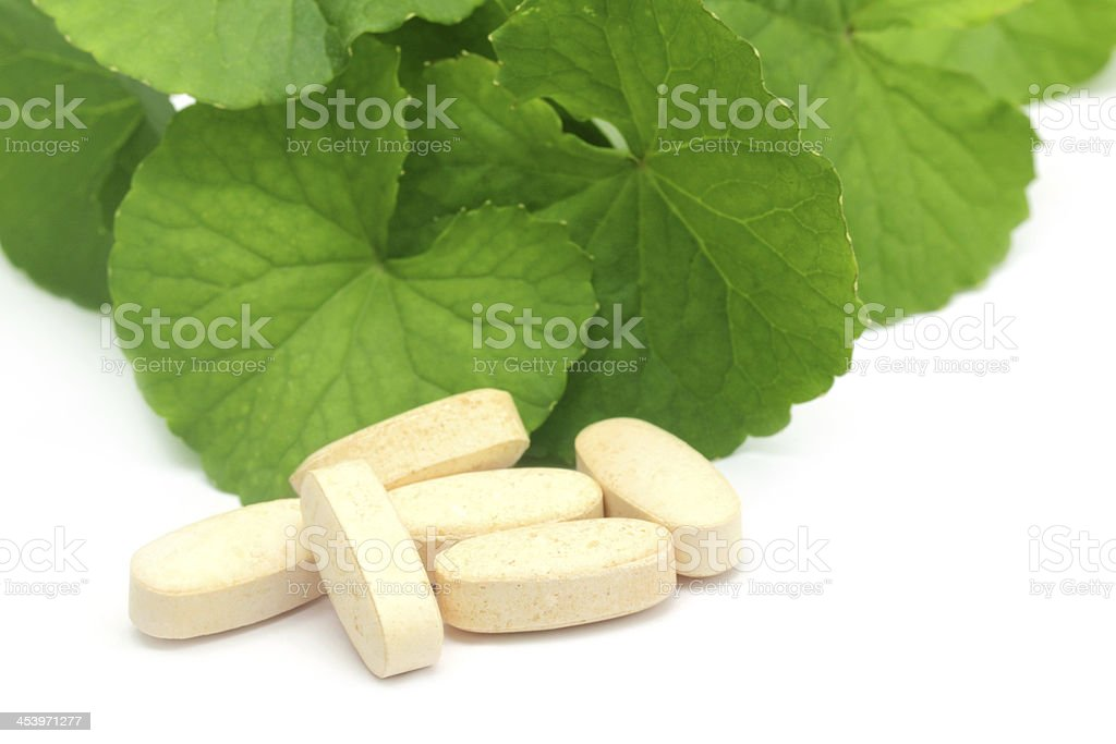 Medicinal thankuni leaves with pills royalty-free stock photo