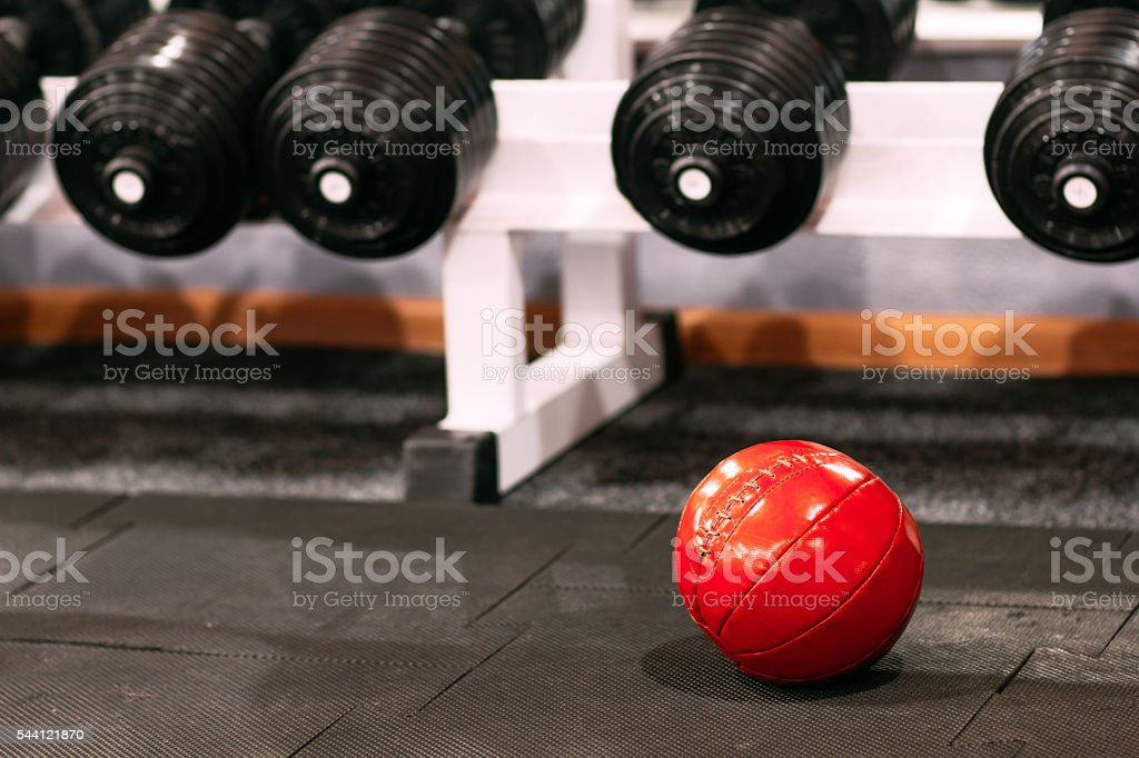 Medicine ball under dumbbells rack at gym stock photo