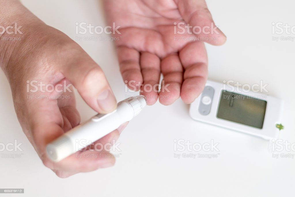 Medicine, diabetes, glycemia, health care and people concept - Close up of man hands using lancet on finger to check high blood sugar level with glucometer or glucose meter at home stock photo