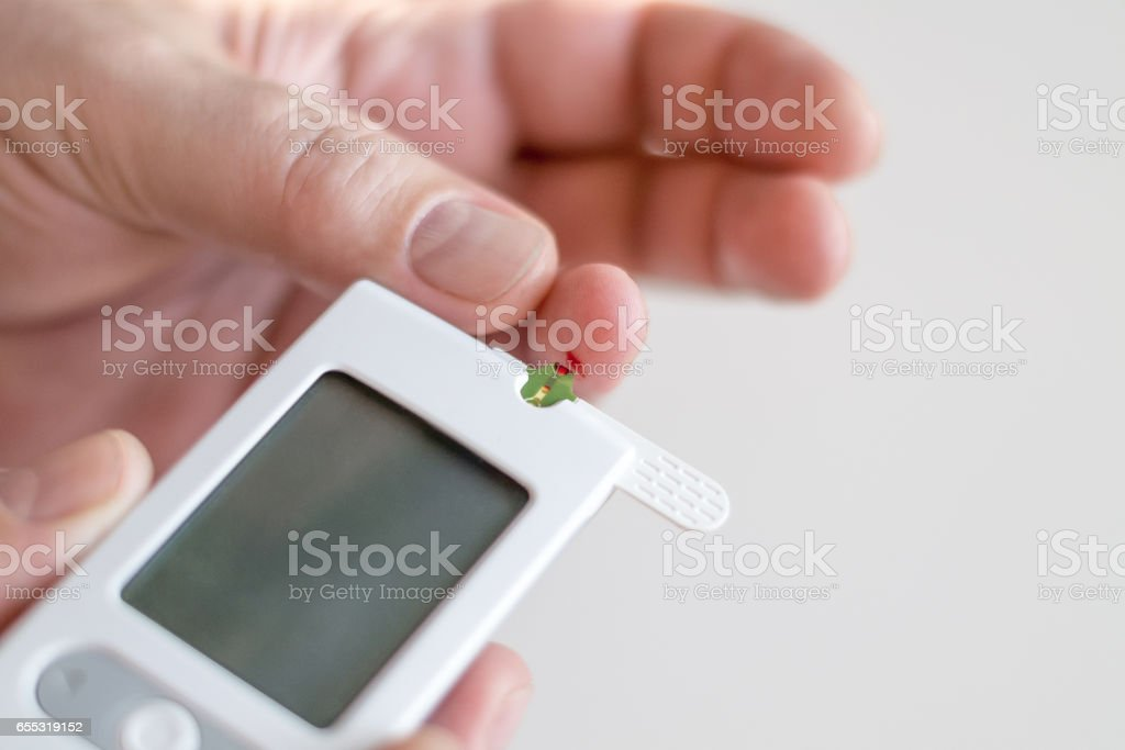 Medicine, diabetes, glycemia, health care and people concept - Close up of man hands testing high blood sugar level with glucometer or glucose meter and test stripe at home stock photo