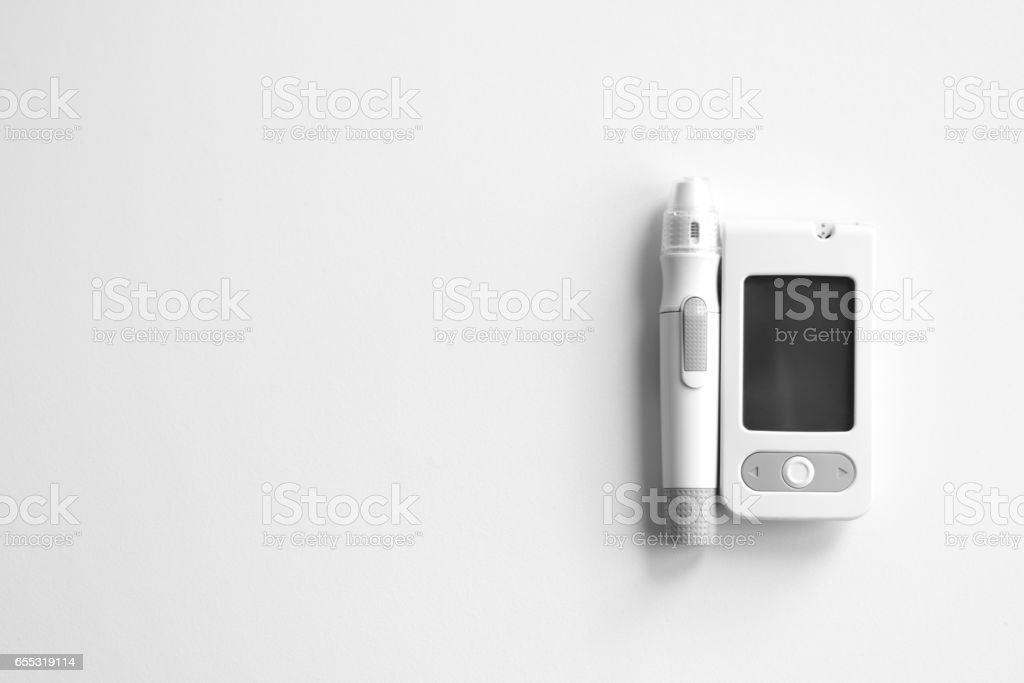 Medicine, diabetes, glycemia, health care and people concept - Glucose meter and lancet device for the diagnosis of glucose stock photo