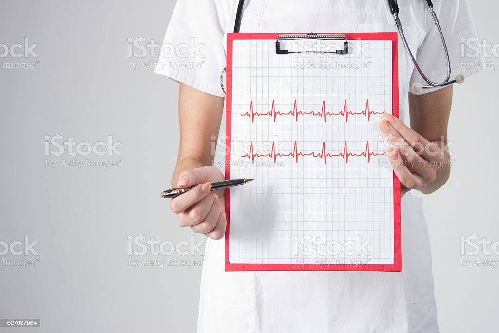 Medicine doctor hands holding cardiogram chart on clipboard pad closeup stock photo
