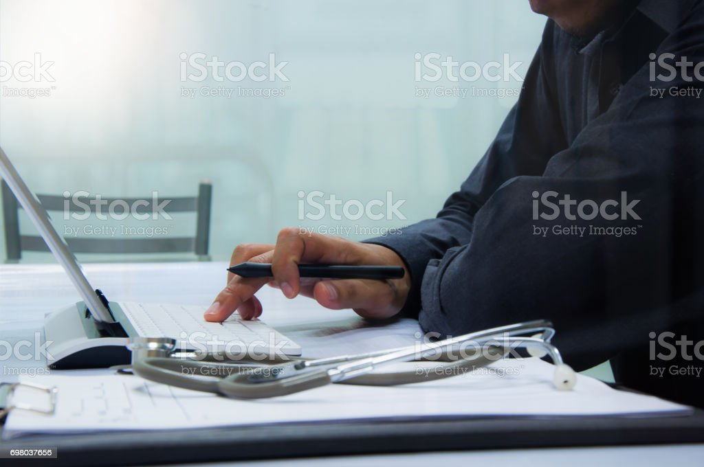 medicine doctor working with computer notebook and digital tablet  at desk in the hospital stock photo