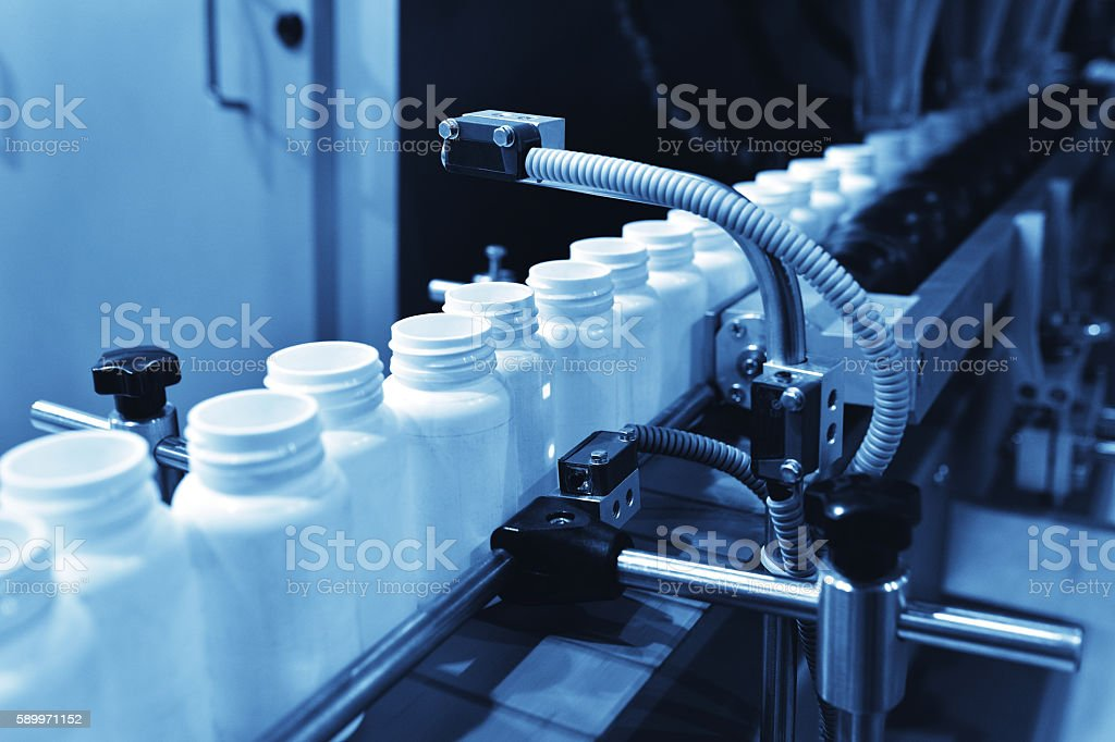 Medicine filling in automated production line stock photo