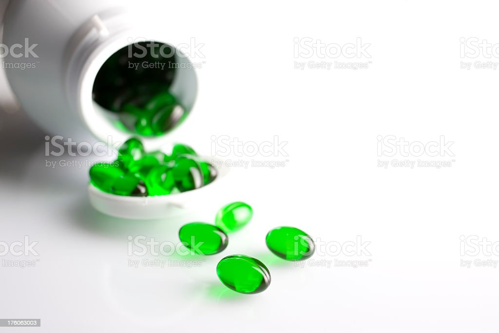 Medicine or food supplement capsules spilling out from a bottle. stock photo