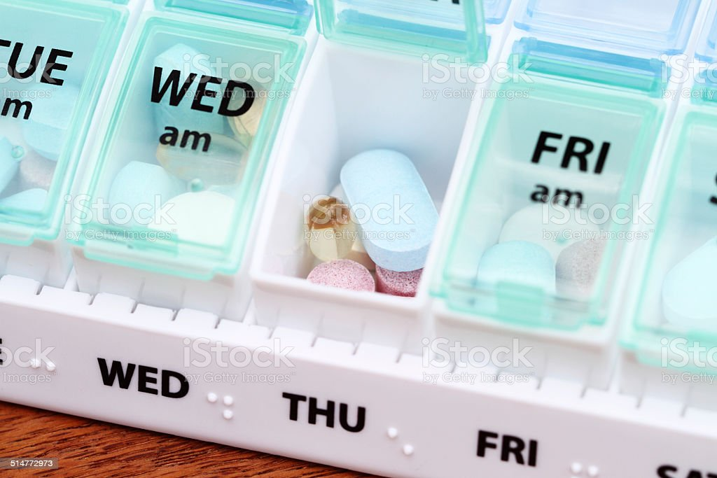 Medicine pill box daily planner with medicines stock photo
