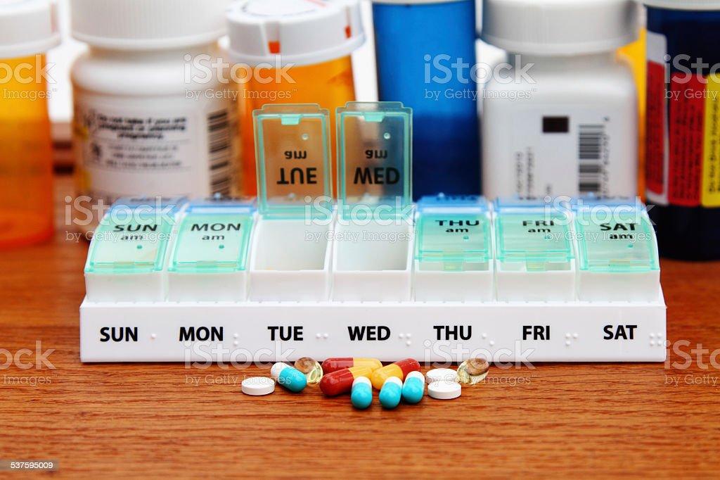 Medicine pill box daily planner with prescription bottles stock photo