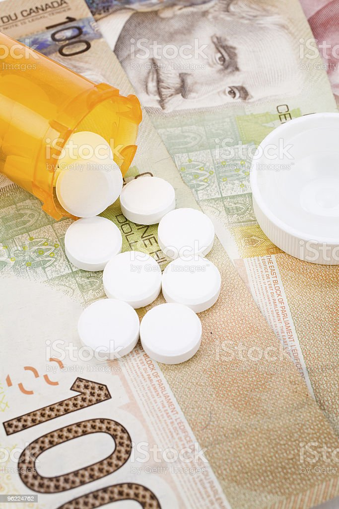 Medicine pills and canadian dollar stock photo