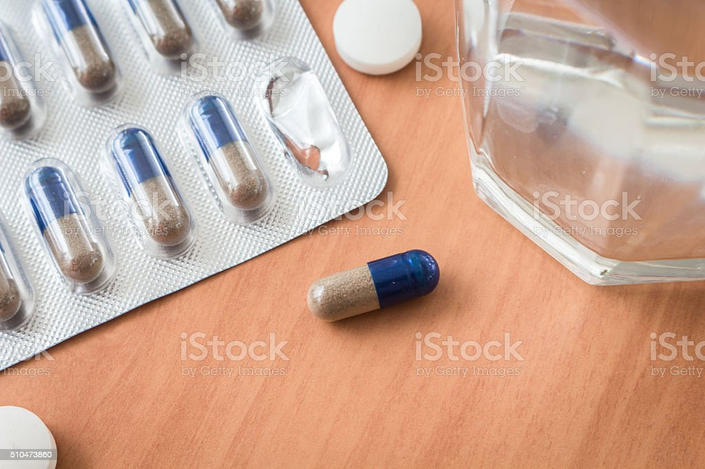 Medicines and water glass on table stock photo
