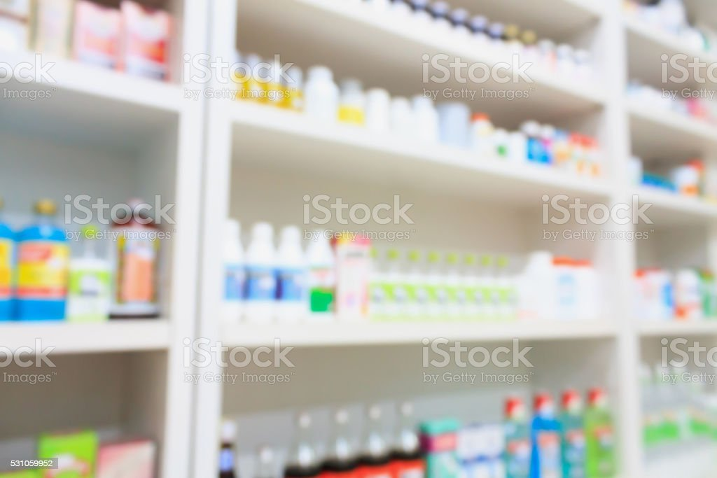 medicines arranged on shelves in the pharmacy blurred background stock photo