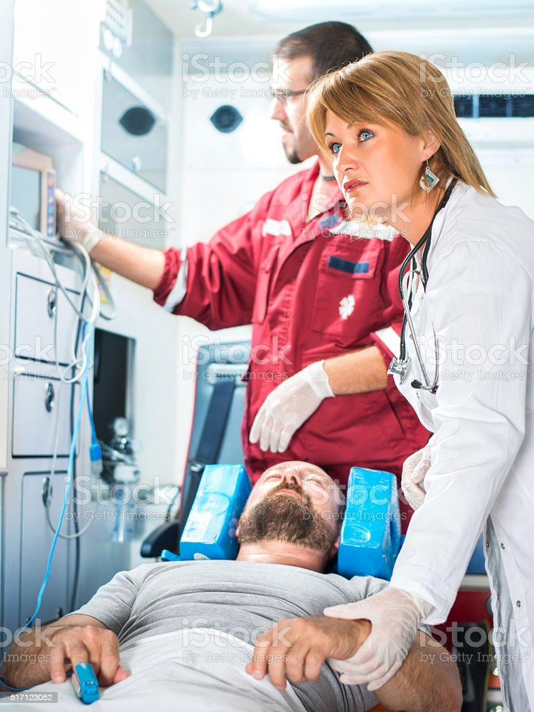 Medics caring for patient in ambulance stock photo